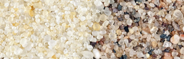 A close-up view shows frac sand on the left and a typical sand of similar grain size on the right. From BanksPhotos, iStockphoto.